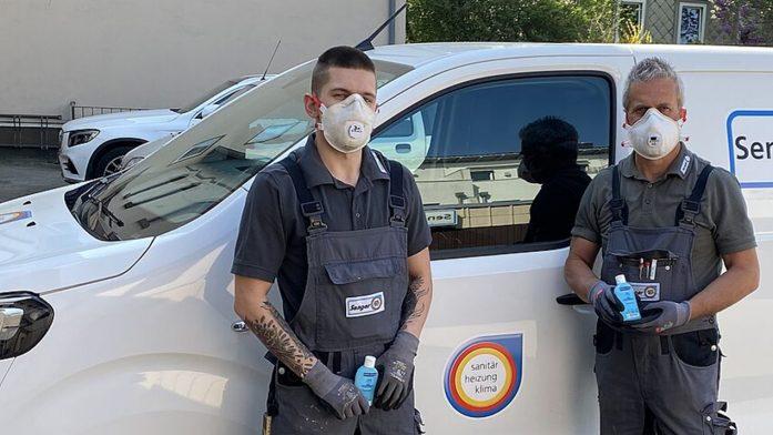 Das SHK-Handwerk während der Corona-Krise: Sanitärhandwerker mit Mundschutz und Desinfektionsmittel